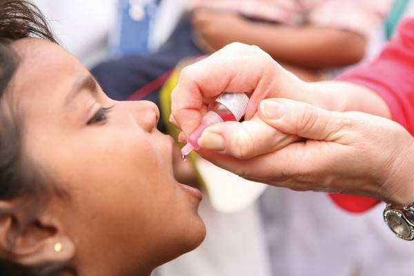 Доктор закапывает АКДС в рот мальчику