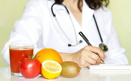 Фрукты лежат на столе перед пишущим что-то врачом