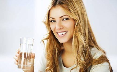 Улыбающаяся девушка держит стакан воды