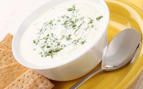 Чашка молочного супа с зеленью и крекерами