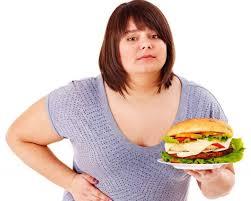 Полная женщина держит огромный гамбургер