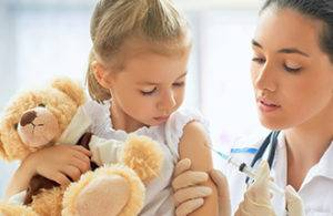 врач делает прививку девочке