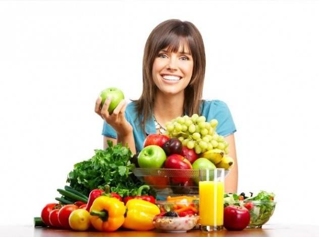Женщина держит в руках фрукты и овощи