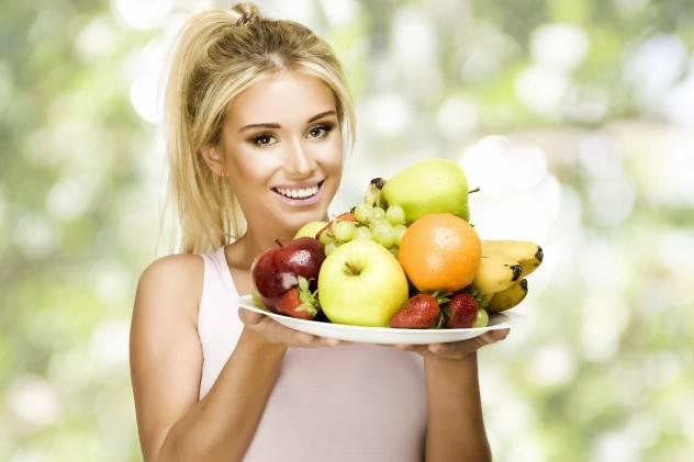 Девушка держит свежие фрукты на блюде