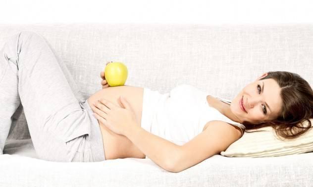 Беременная женщина лежит и держит в руке яблоко