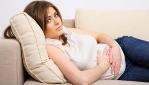 Девушка лежит на диване в плохом самочувствии