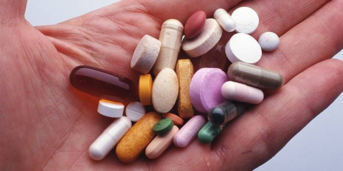 Мужчина держит в руке таблетки