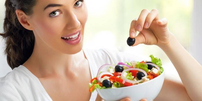 Девушка держит тарелку с салатом в руках