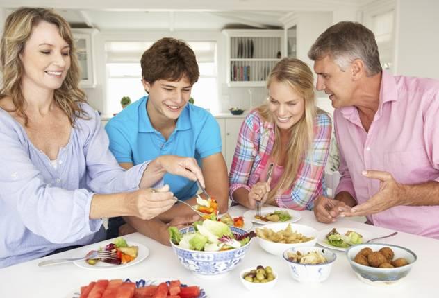 Семья сидит за столом и кушает здоровую пищу