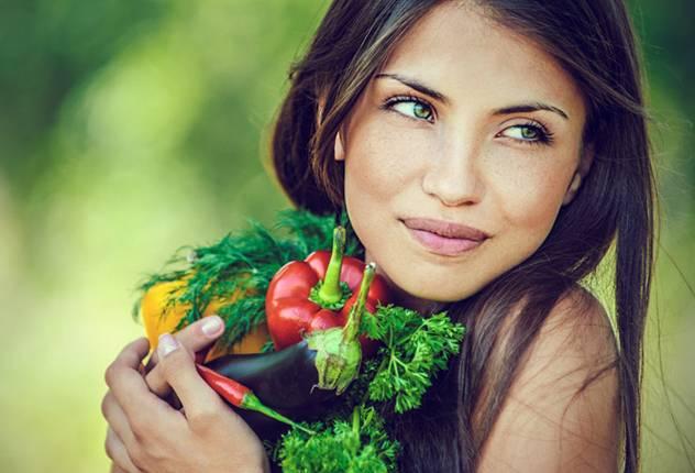 Девушка держит в руках полезные овощи и зелень
