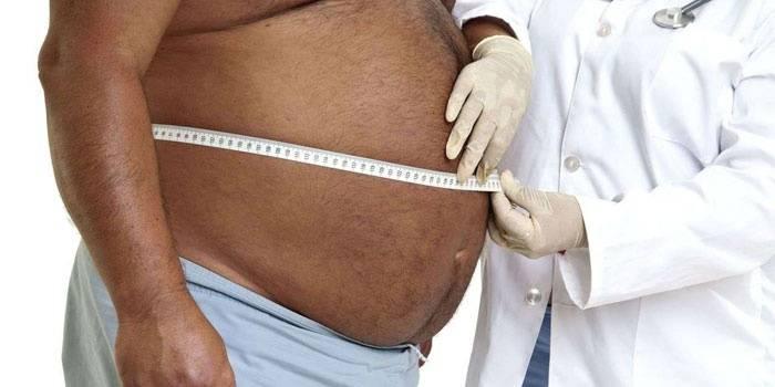 Мужчине измеряют живот сантиметром